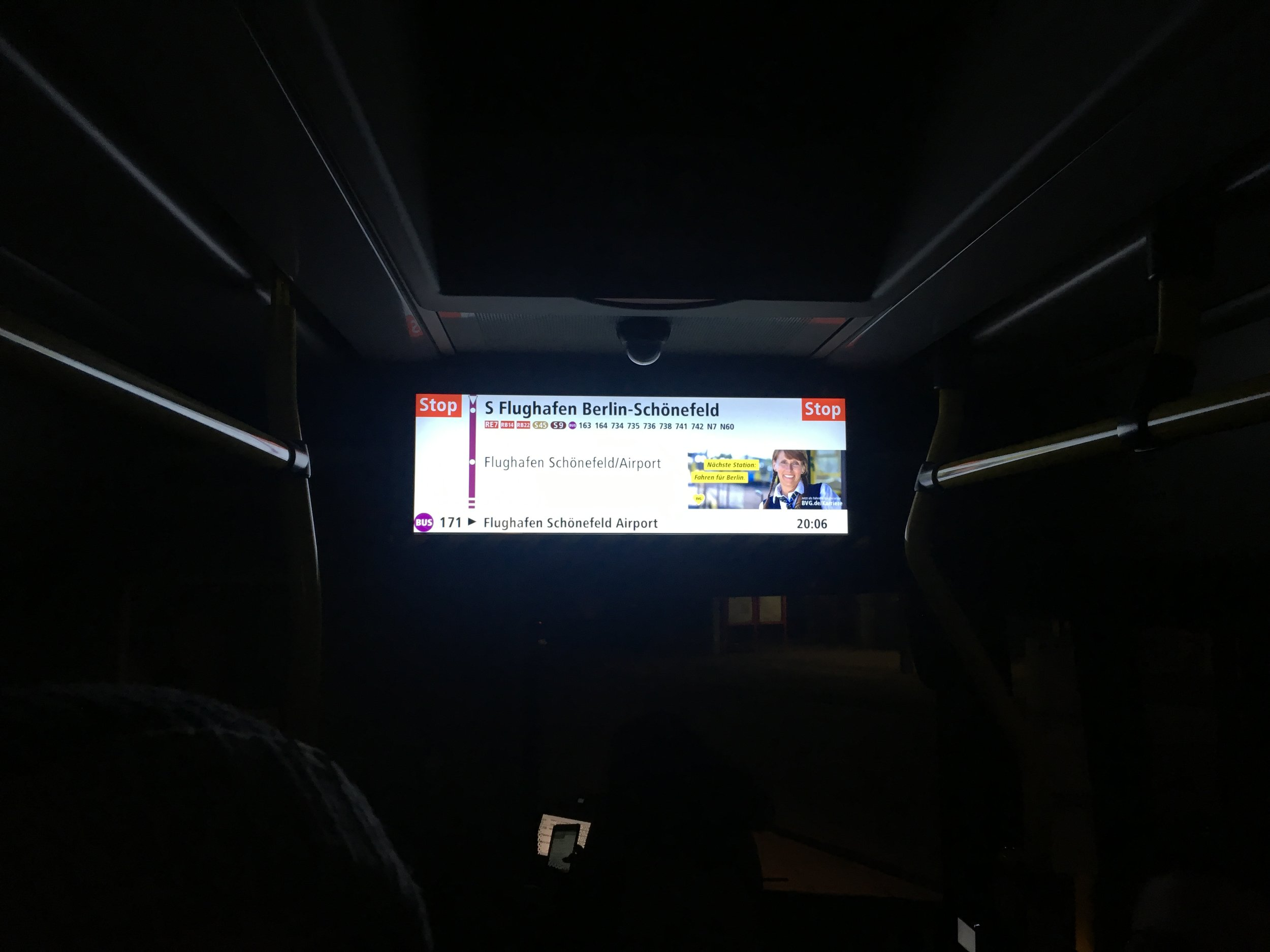 The screen on the public bus displaying the next station as well as the final destination.